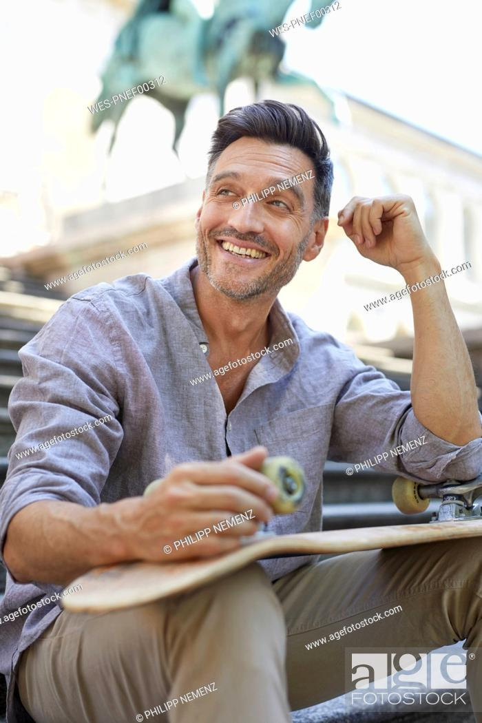 Stock Photo: Portrait of laughing mature man with skateboard sitting on stairs.