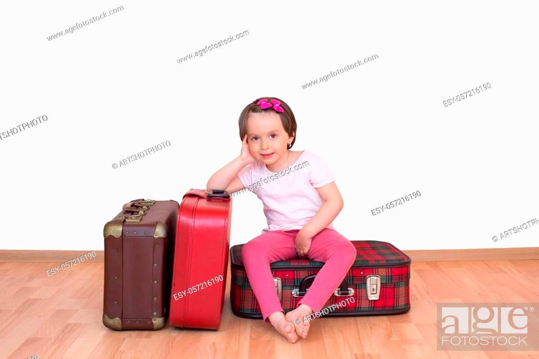 Stock Photo: Little girl sitting on vintage suitcase isolated.