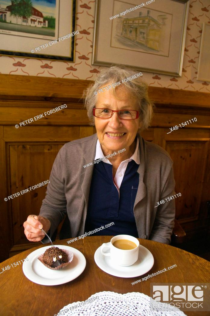 Stock Photo: Female in her early 70s having coffee and cake Finland Europe.