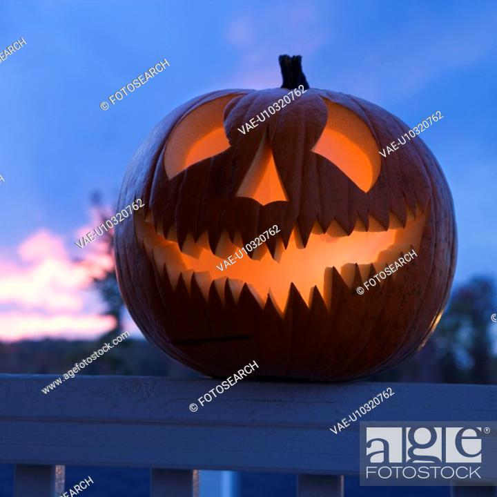 Stock Photo: Carved Halloween pumpkin perched on porch railing.