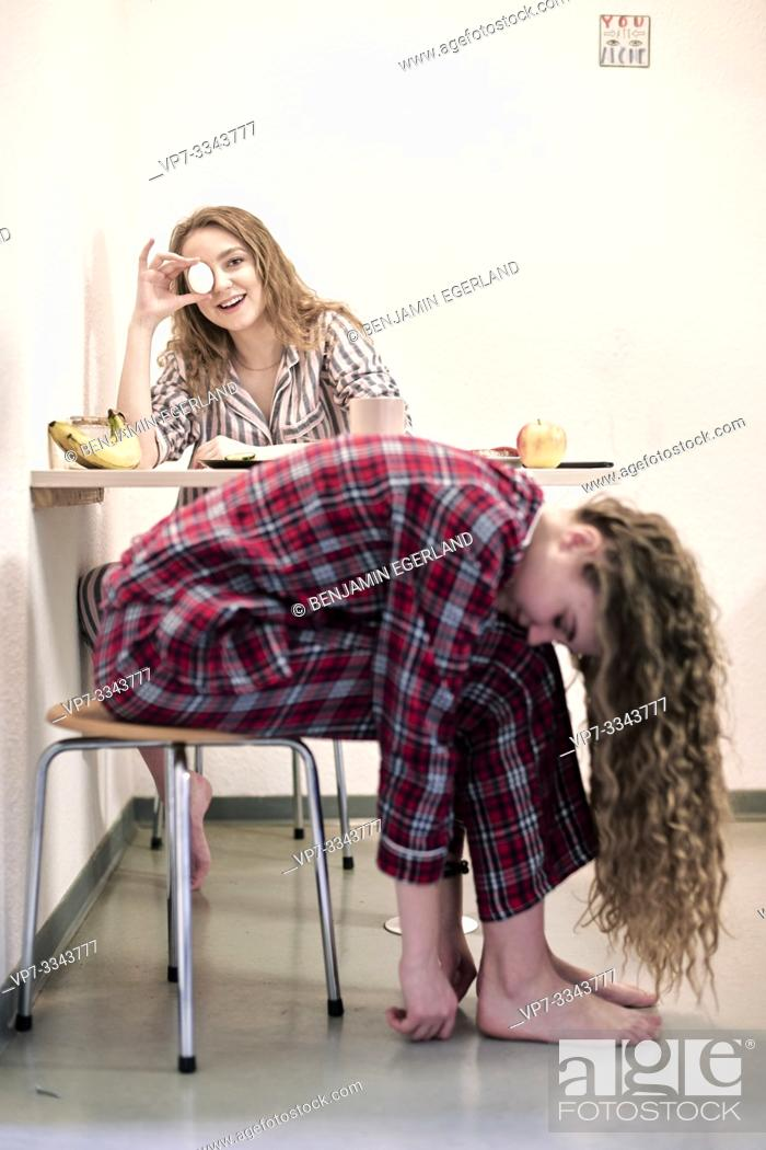 Stock Photo: two young women in pyjamas at breakfast table in kitchen of shared student dormitory.