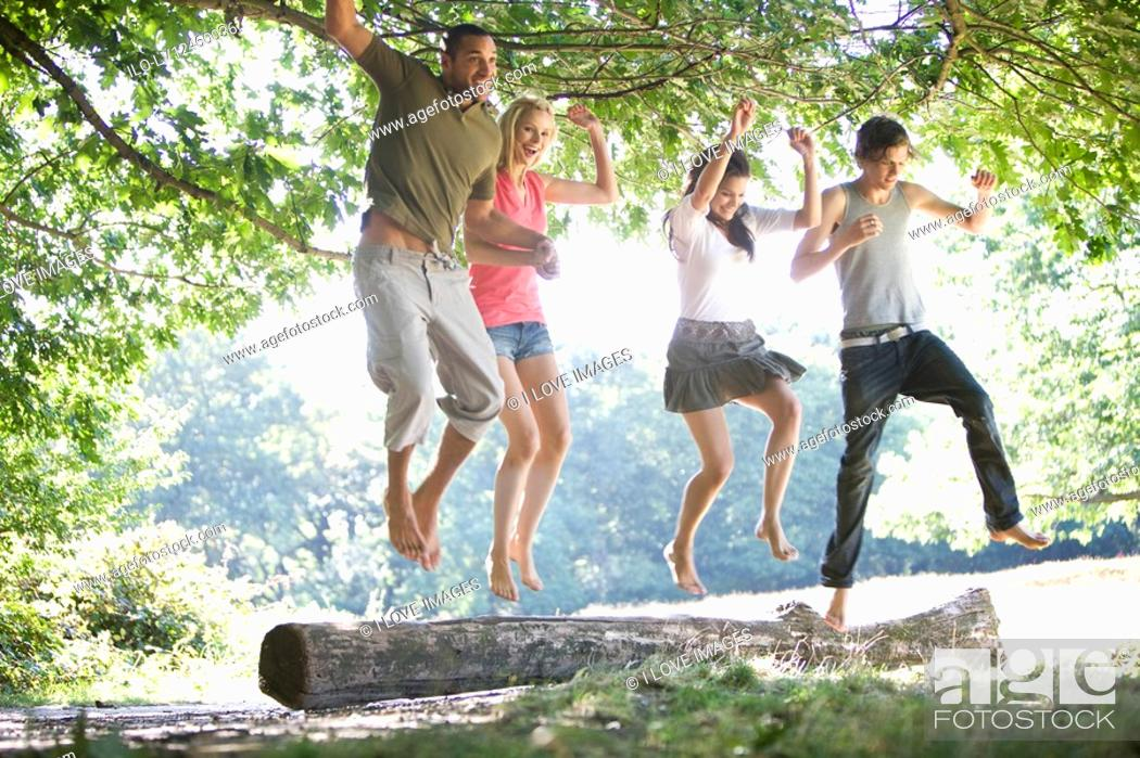 Stock Photo: Four friends jumping from a log.