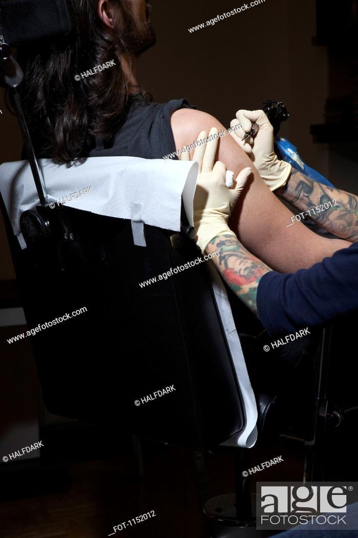 Stock Photo: A tattoo artist preparing to tattoo a man's bare arm.