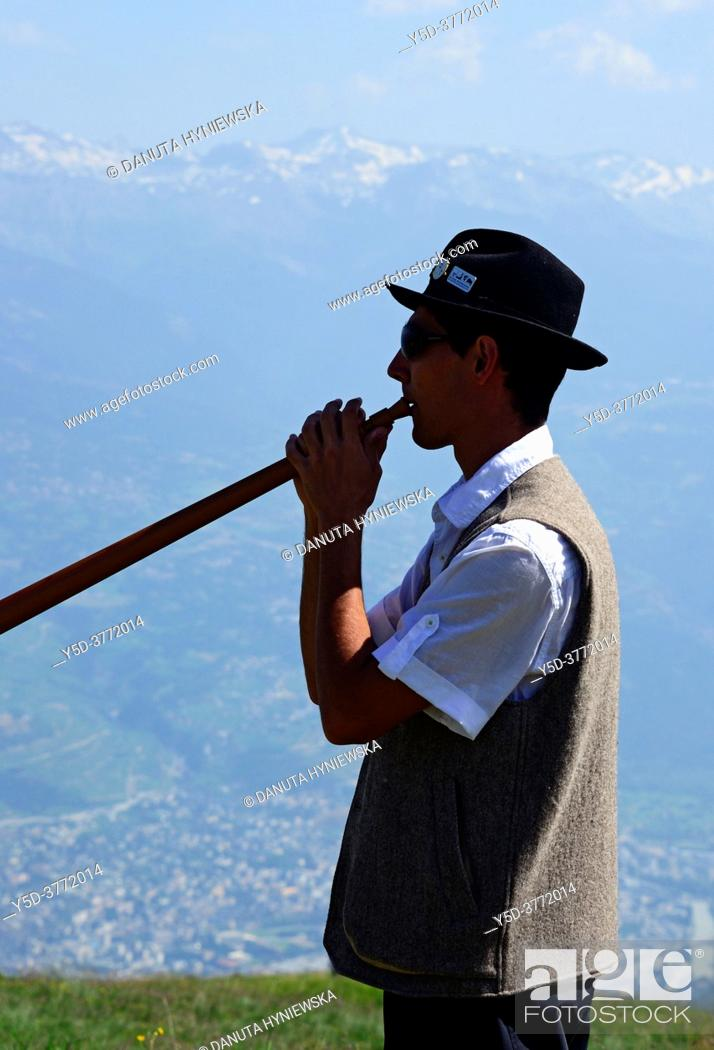 Stock Photo: young man playing alphorn in Swiss Alps, Nendaz, canton Valais, canton Wallis, Switzerland, Europe.