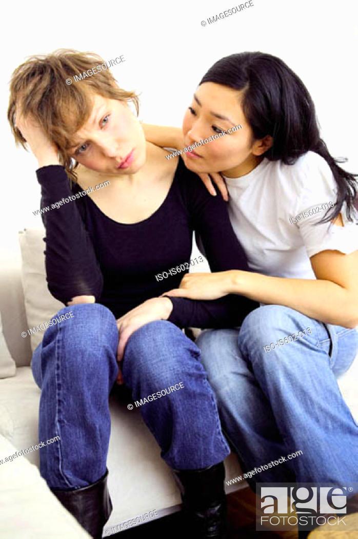 Stock Photo: Woman comforting friend on sofa.
