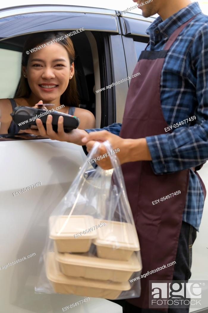 Stock Photo: Asian woman customer make mobile payment contactless technology on drive thru food service restaurant while picking up. Drive through is new normal more popular.