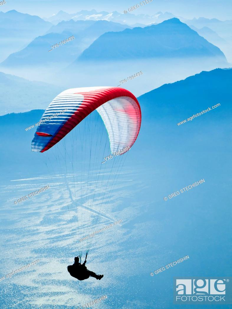 Stock Photo: A man paragliding in the Swiss Alps near Mount Rigi.