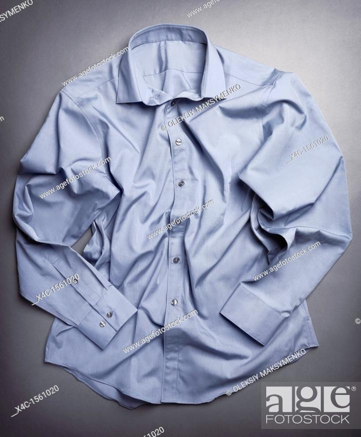 Stock Photo: Photo of artistically crumpled mens dress shirt on gray background.