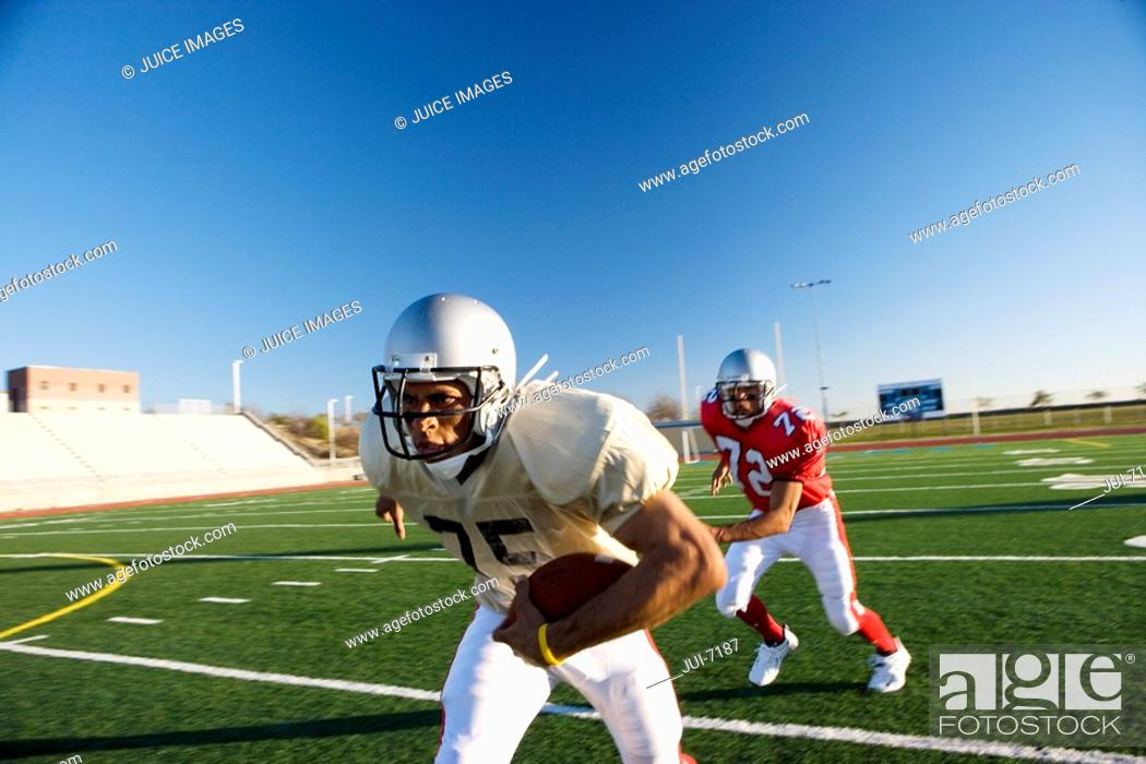Stock Photo: American football player chasing opposing player running with ball during competitive game.