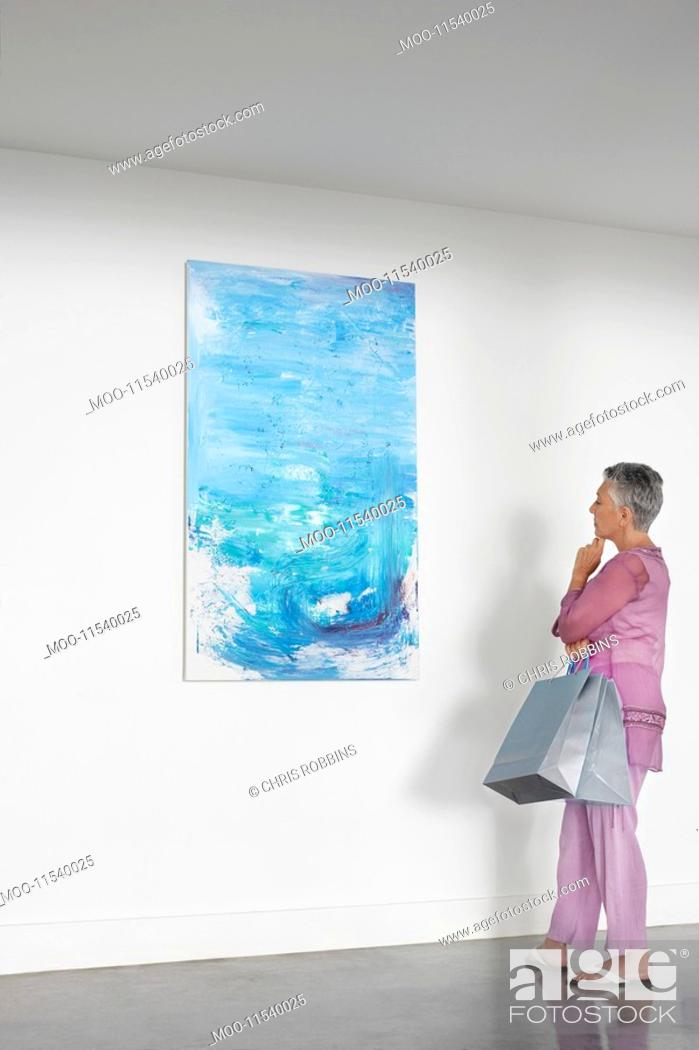 Stock Photo: Woman observing painting in art gallery.