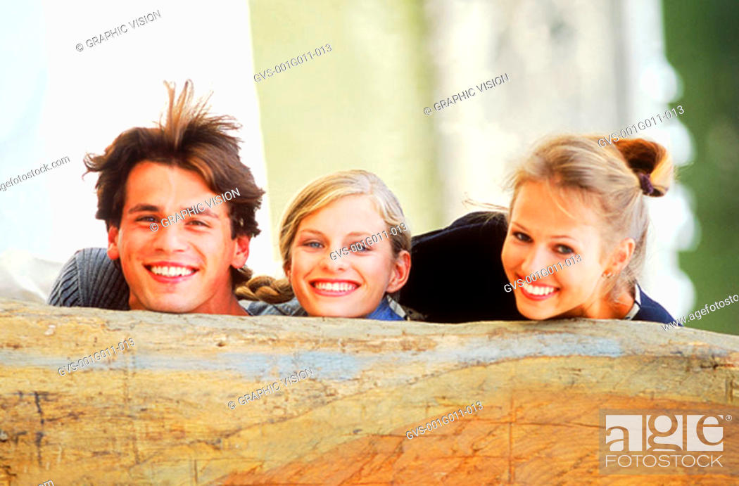Stock Photo: Portrait of a Young man and two young women behind a wooden log.