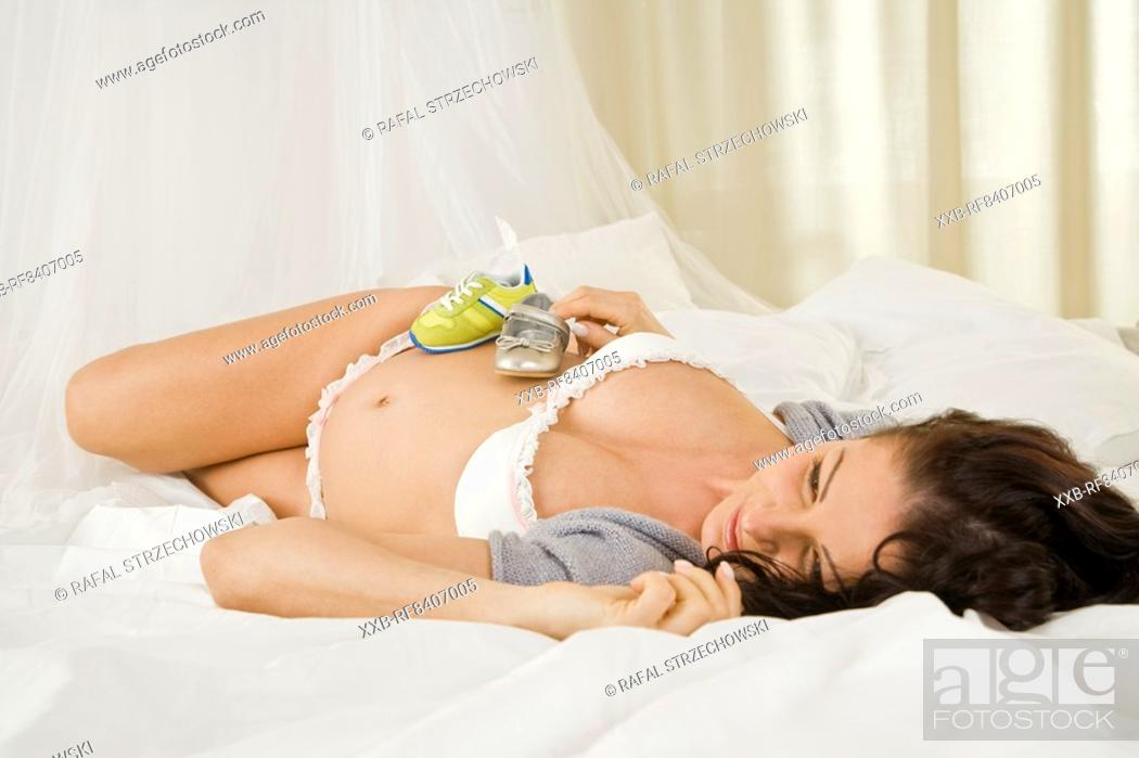Stock Photo: preganant woman holding baby shoes.