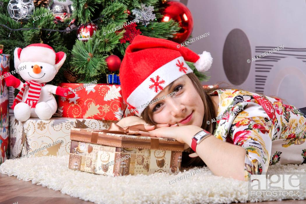 Stock Photo: The girl lying on the carpet around the Christmas tree. In her hands a big box with a present. The girl looks frame.