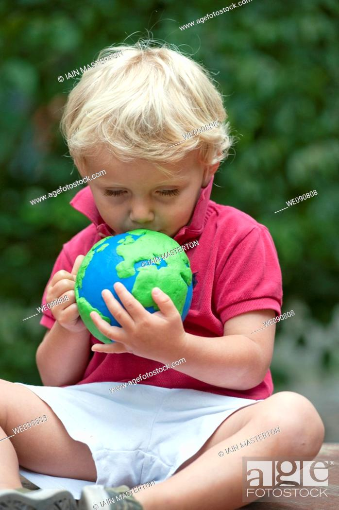 Stock Photo: young boy holding and kissing a model of planet Earth.