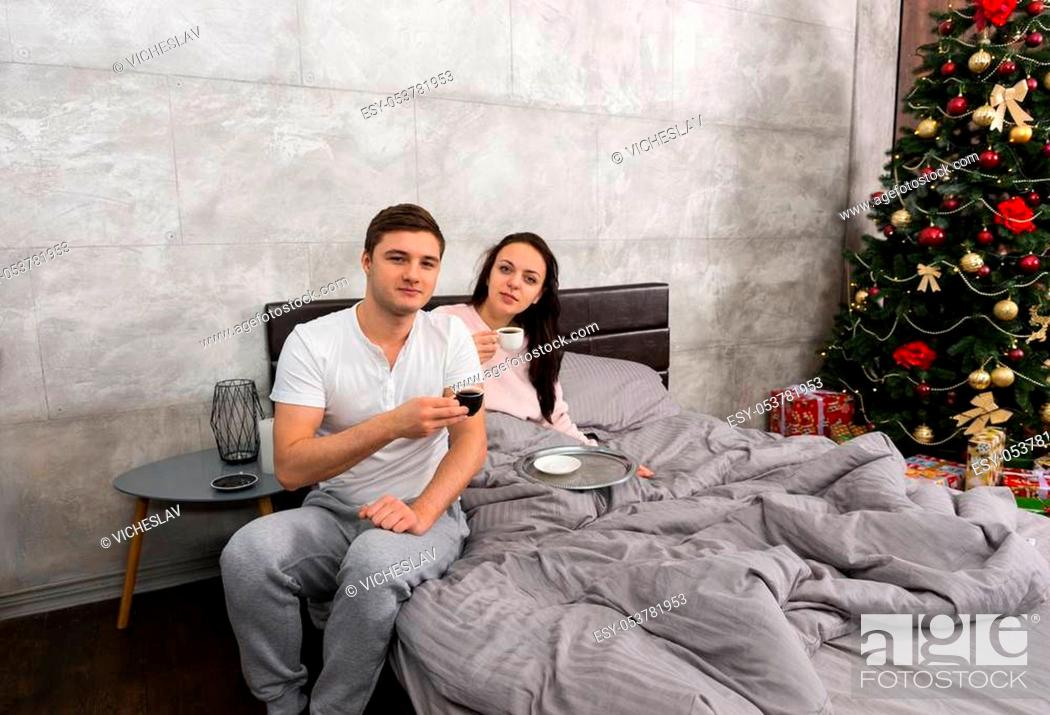 Stock Photo: Young couple drinking coffee in a bed, wearing pajamas, in the bedroom with Christmas tree and presents.