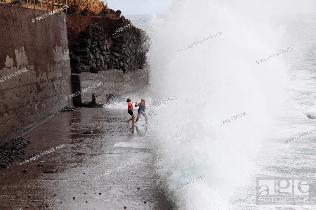 Stock Photo: girls playing at the beach and have fun with the spray of waves, Madeira, Portugal, Europe.