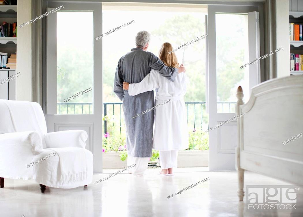 Stock Photo: Couple in bathrobes standing in balcony doorway.