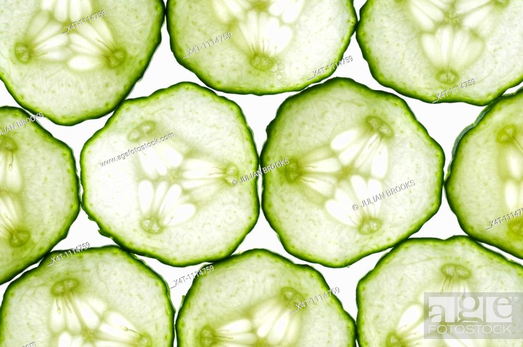 Stock Photo: thin slices of cucumber lit from behind, edges touching making a tiled pattern.