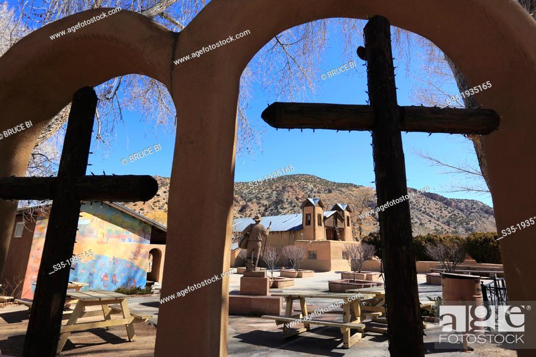 Stock Photo: Crosses in the garden with the historical catholic chapel of Santuario de Nuestro Senor de Esquipulas aka El Santuario de Chimayo in the background.