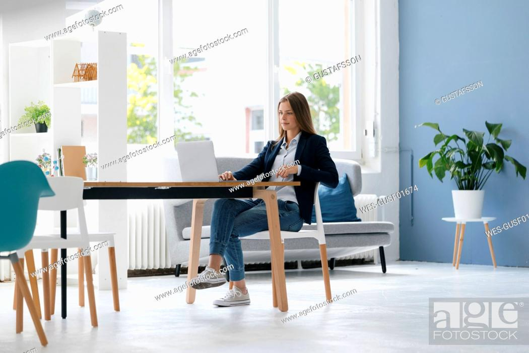 Stock Photo: Young businesswoman sitting in office, using laptop.
