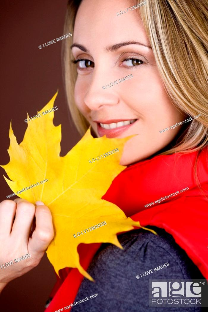 Stock Photo: A mid adult woman holding an autumn leaf, smiling.