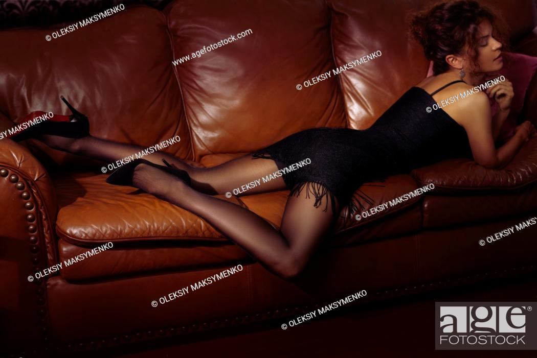 Stock Photo: Sensual portrait of a beautiful sexy woman lying on a brown leather couch wearing a short black dress, black stockings and high heel shoes.