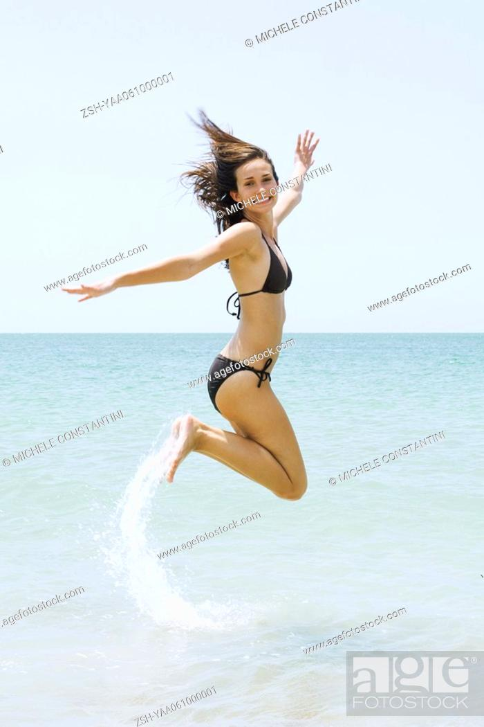 Stock Photo: Young woman in bikini at the beach, jumping in the air, smiling at camera.