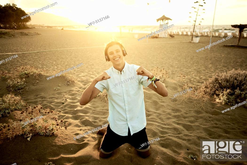 Photo de stock: Young man with headphones kneeling on beach, in holiday destination Malia, Crete, Greece.