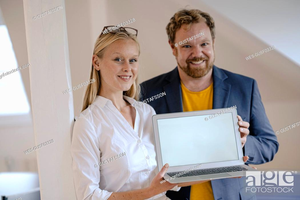 Stock Photo: Portrait of confident businessman and businesswoman in office presenting laptop.