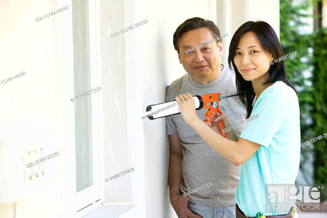Stock Photo: Mid adult man standing with a young woman using a caulk gun.