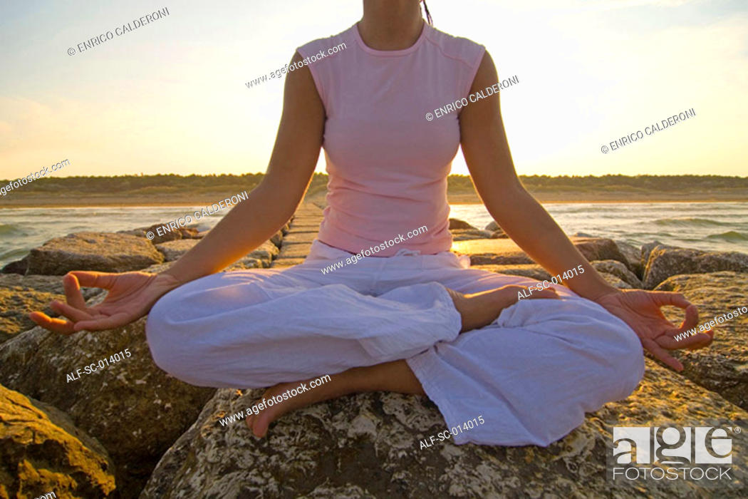 Stock Photo: Young woman doing yoga exercises by sea.