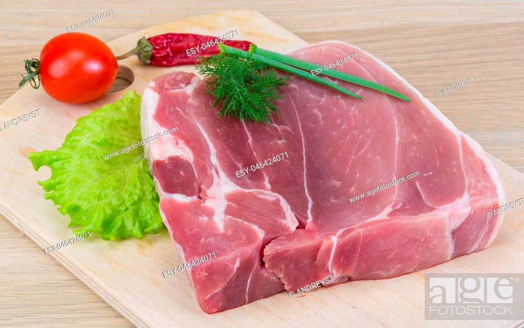 Imagen: Raw pork meat ready for cooking with herbs.