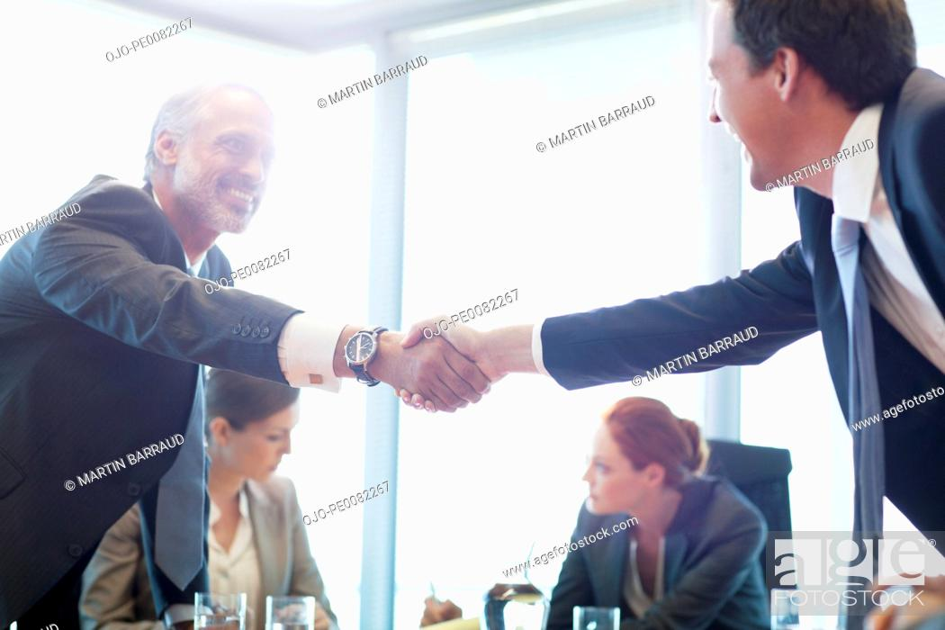 Stock Photo: Businessmen shaking hands in conference room.