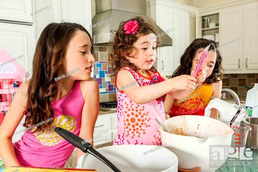 Stock Photo: Sisters baking in kitchen.