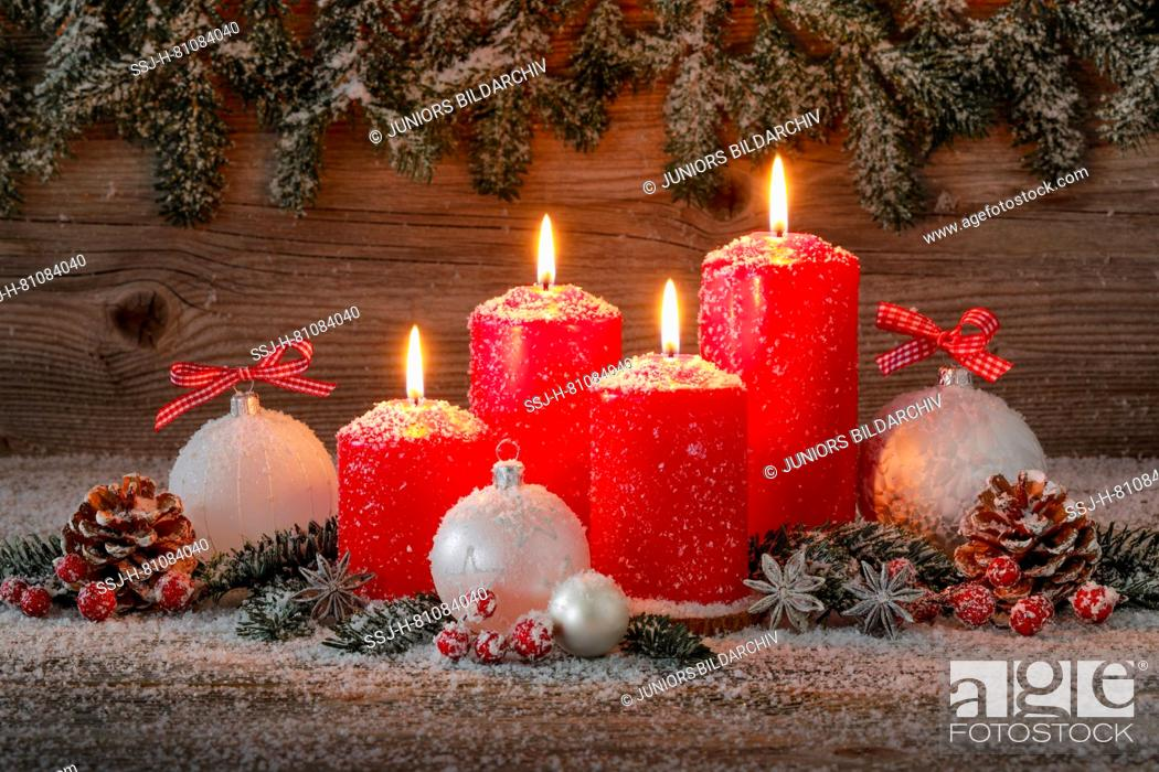 Stock Photo: Natural Christmas decoration. Four red burning candles with christmas baubles and cones. Switzerland.