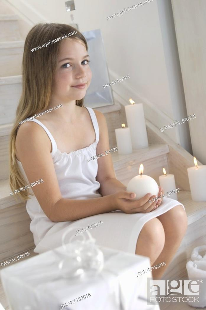 Stock Photo: Christmas, little girl sitting indoors, holding a candle, indoors.