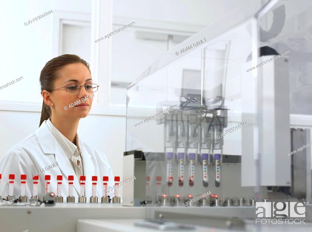 Stock Photo: Scientist watching test tubes in machine.