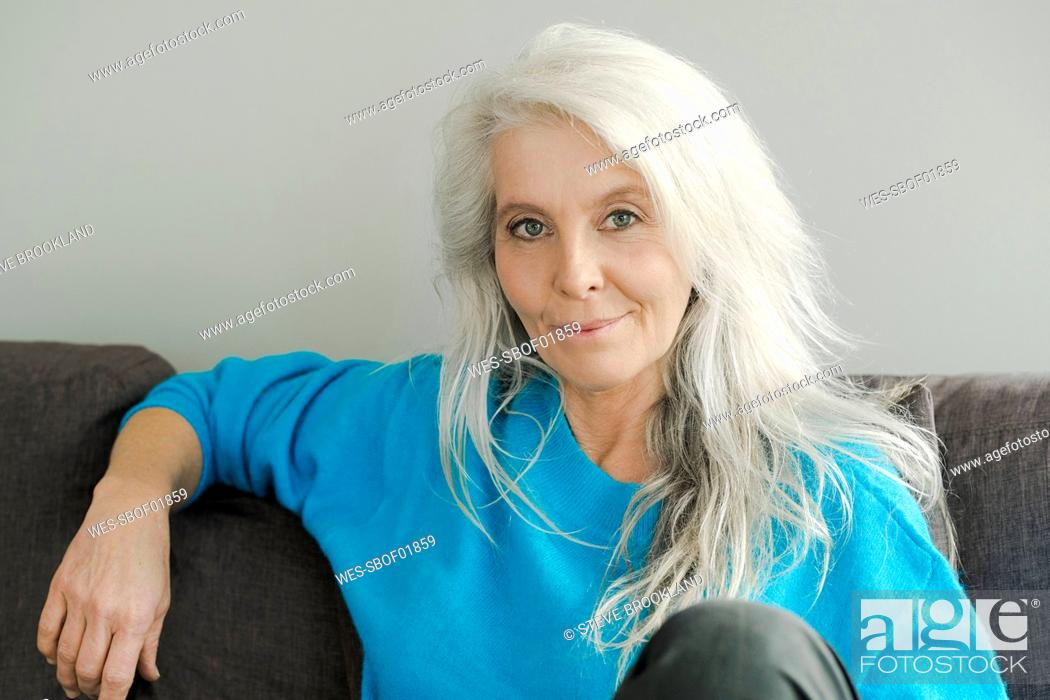 Imagen: Portrait of smiling mature woman sitting on the couch at home.