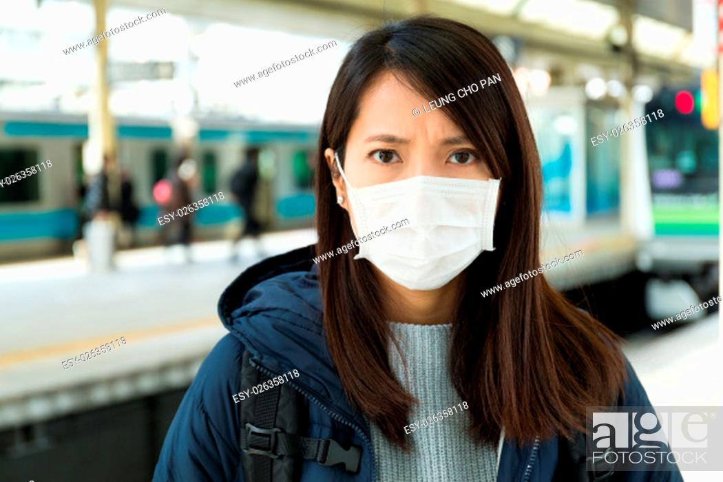 Stock Photo: Woman wearing face mask at train station.