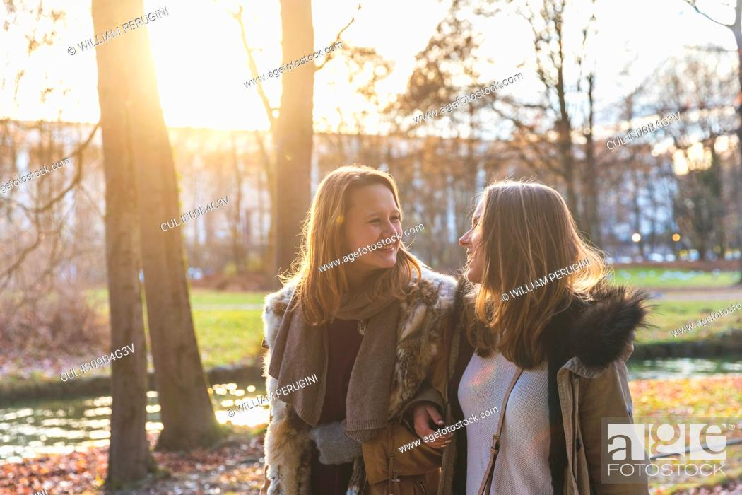 Imagen: Two young female friends strolling on park riverside.