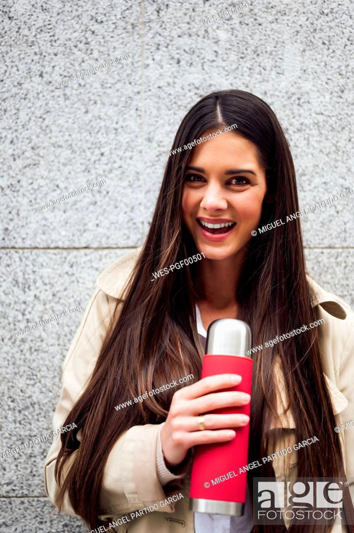 Stock Photo: Beautiful woman holding bottle in front of wall.