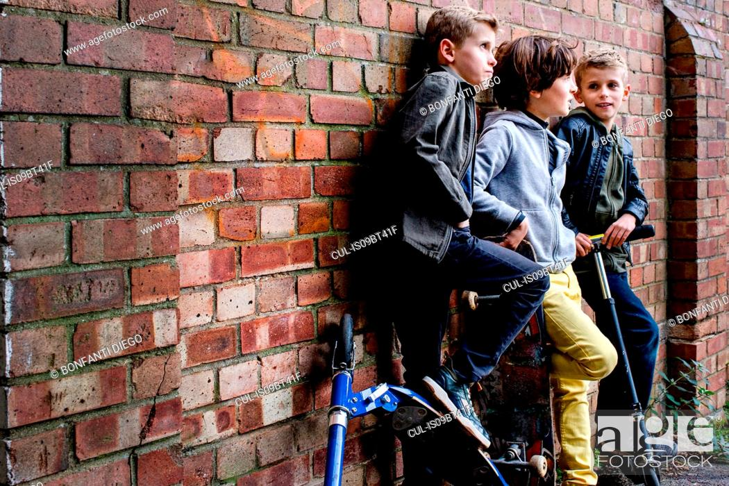 Stock Photo: Boys leaning against brickwall.