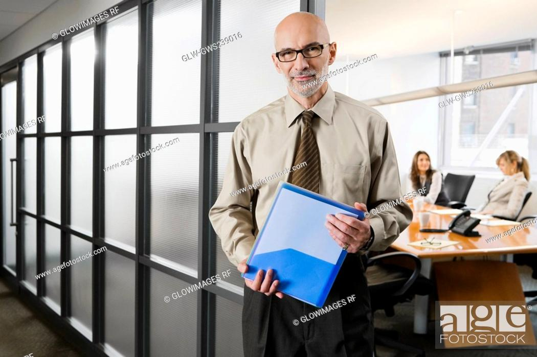 Stock Photo: Portrait of a businessman holding a file.