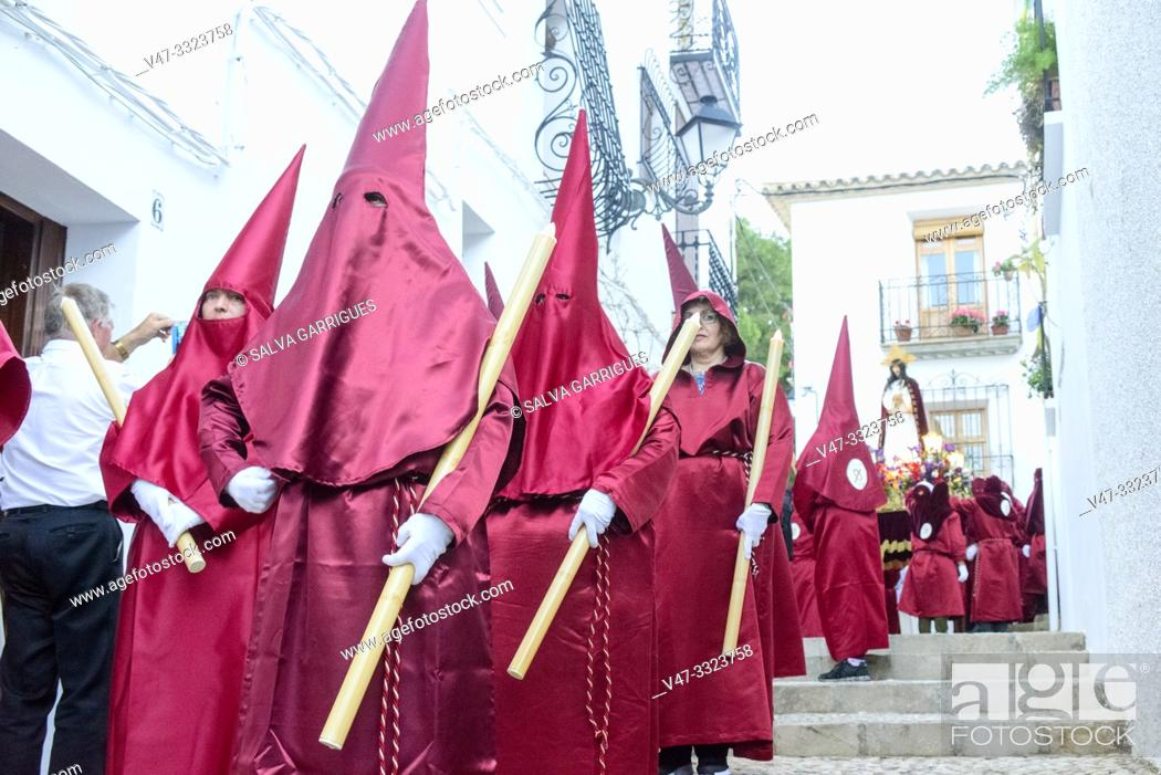 Stock Photo: Cofrades with the tunic and the red procession cap through the streets of Altea.