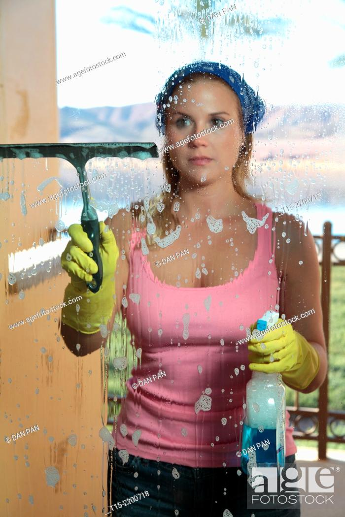 Stock Photo: A young woman cleaning the window.