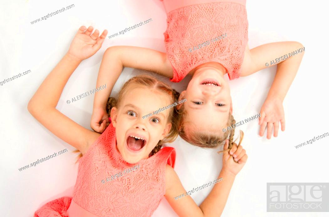 Stock Photo: Two girls sisters in the same clothes lie on a white surface next to a head-to-head look at the picture and smiling.