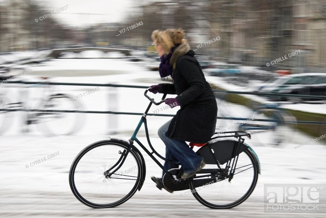Stock Photo: Woman cycling in winter, Amsterdam, the Netherlands.