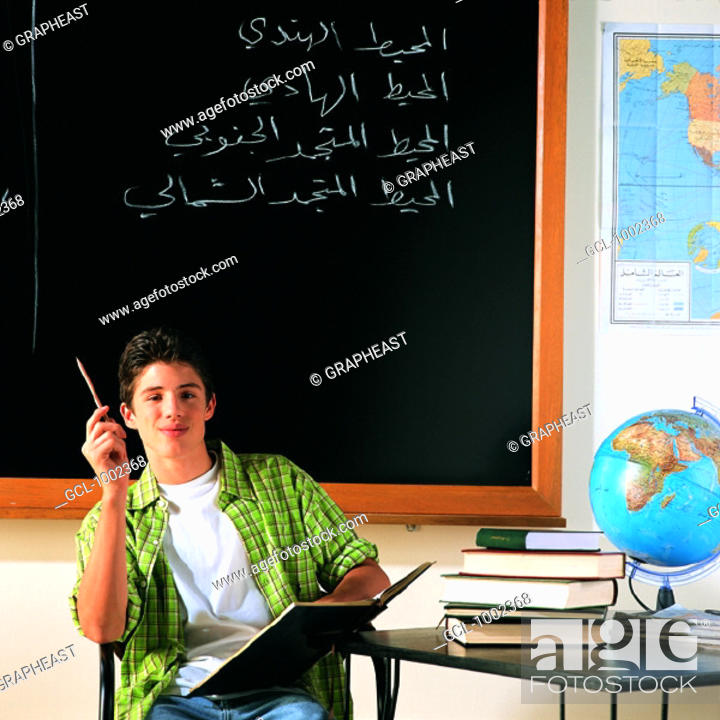Stock Photo: Pupil in classroom with books and globe.