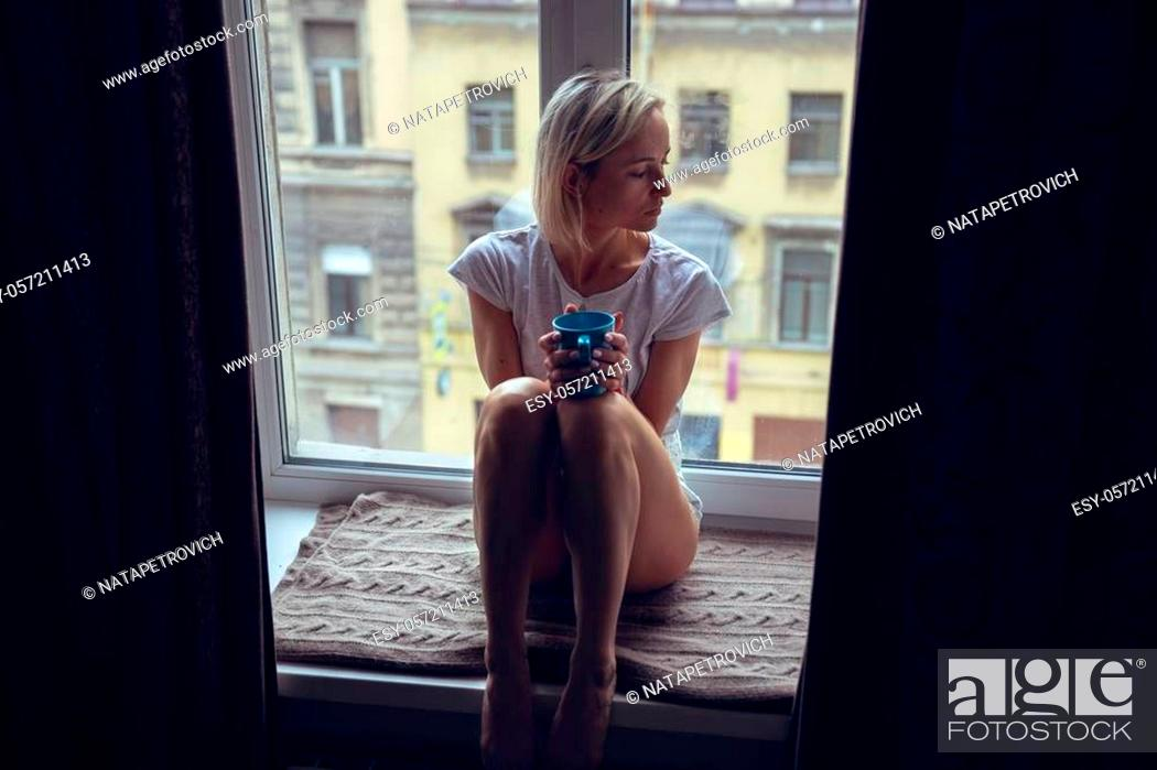 Stock Photo: Resting and thinking woman. Calm girl with cup of tea or coffee sitting and drinking on the window-sill at home. Side view.