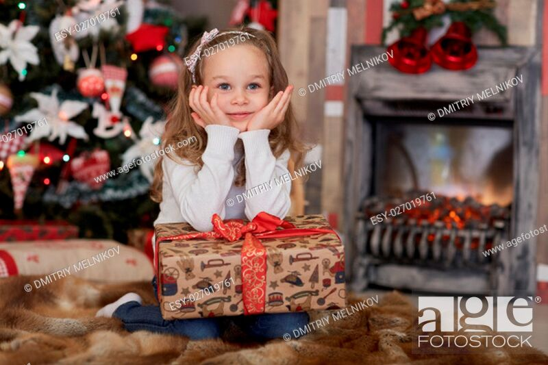 Stock Photo: Happy pretty girl with gift box lies near Christmas tree in the room of the house. Merry Christmas and New Year.